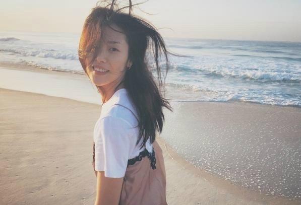 (点小图查看大图) 照片中,她漫步海边,长发飞舞,美得像一幅画.