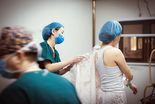 (点小图查看大图) 进入手术室,医生为杨希月脱去全身衣服.